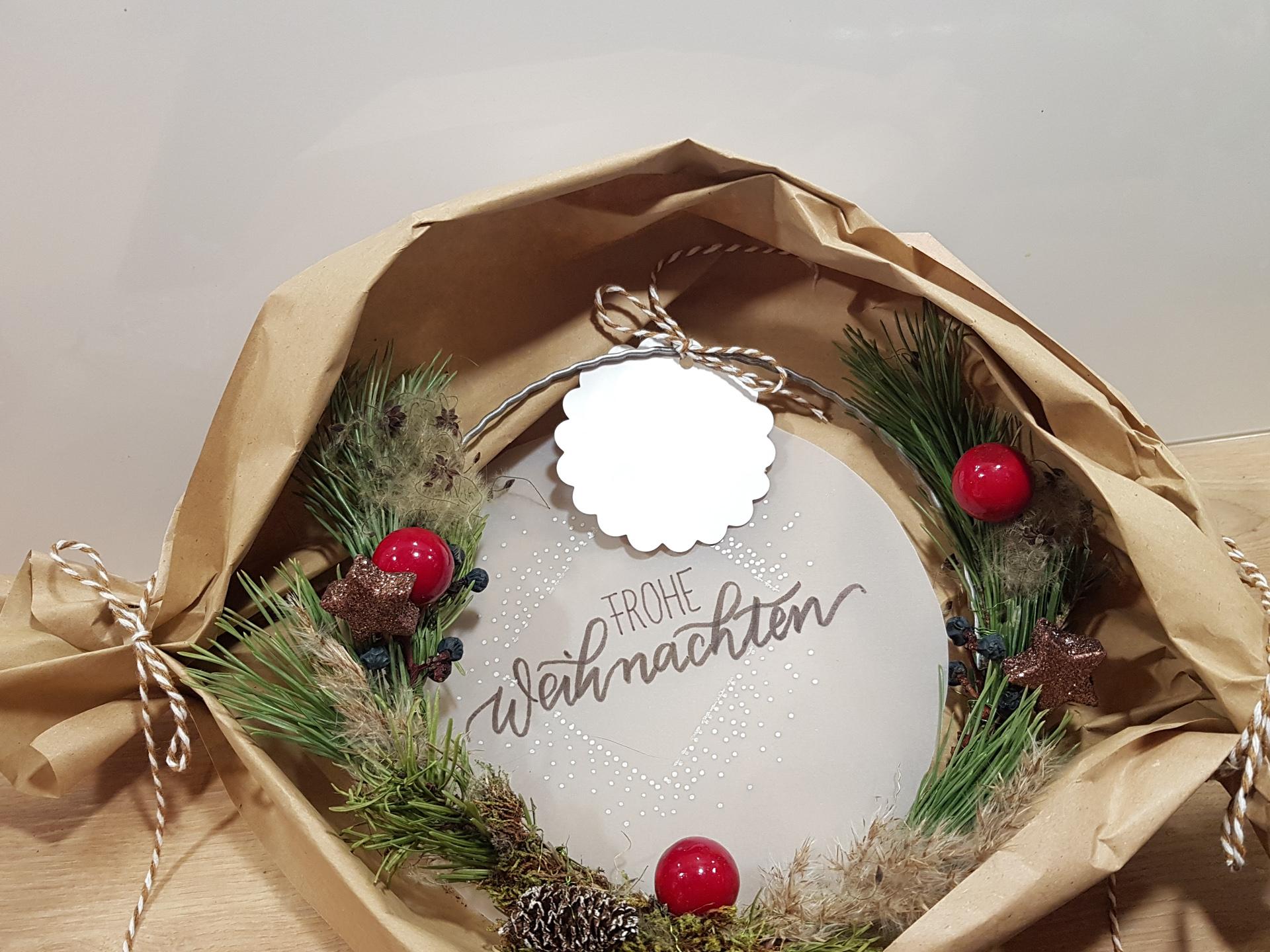 """Kleiner selbstgebundener Weihnachtskranz mit lila Christbaumkugeln. Im Hintergrund steht auf Transparentpapier """"Frohe Weihnachten""""."""