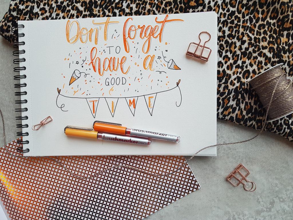 """Lettering mit Verzierungen auf weißem Papier mit orangen Stiften und der Aufschrift """"Don't forget to have a good time"""""""