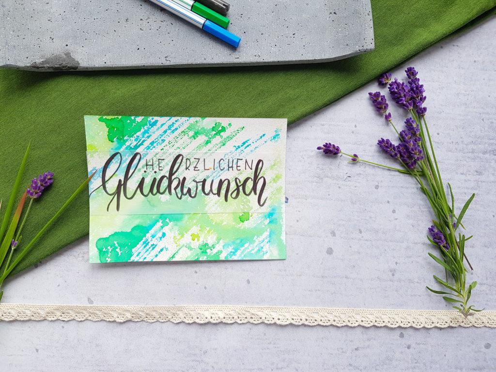 """Eine Glückwunschkarte zum Geburtstag auf Aquarellpapier. Auf diesem ist ein Blumenstrauß im Watercolor-Style gemalt. Über dem Strauß ist mit Transparentpapier """"Herzlichen Glückwunsch"""" gelettert."""