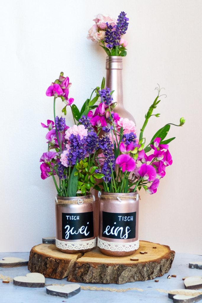 Zwei selbstbesprühte Blumenvasen in rose, welche dekoriert und mit einer schwarzen Tafelfolie beklebt wurde. Auf der Mitte der Vase ist die Folie mit weißem Stift belettert mit den Tischnummern.