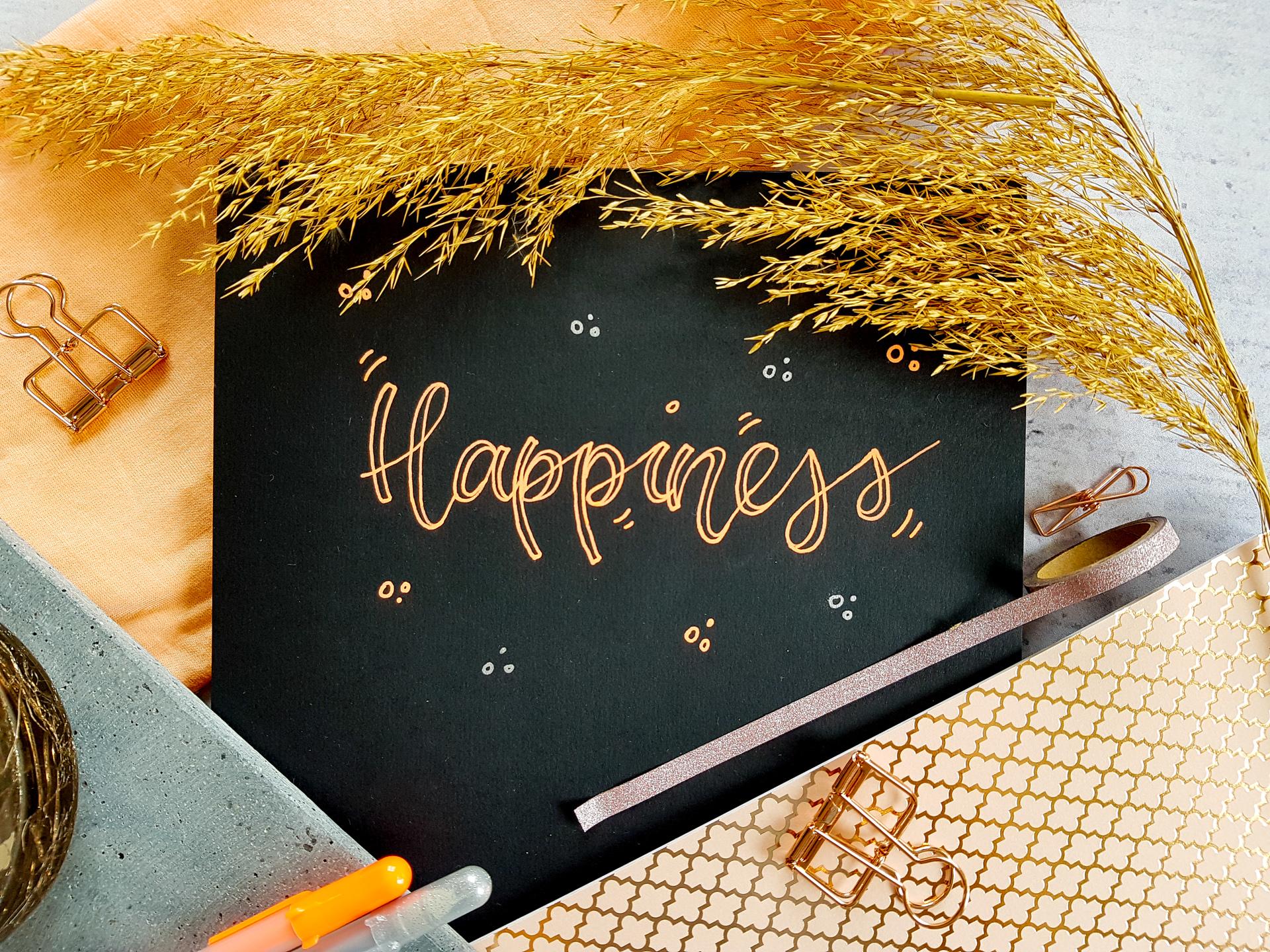 """Ein Lettering mit dem Wort """"Happiness"""" mit orange-leuchtenden Stiften im Faux-Calligraphie-Style auf schwarzem Papier"""