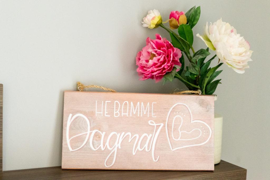 """Holzschild aus Kiefernholz mir rosegoldenem Hintergrund mit der Aufschrift """"Hebamme Dagmar"""" in weißer Schrift."""