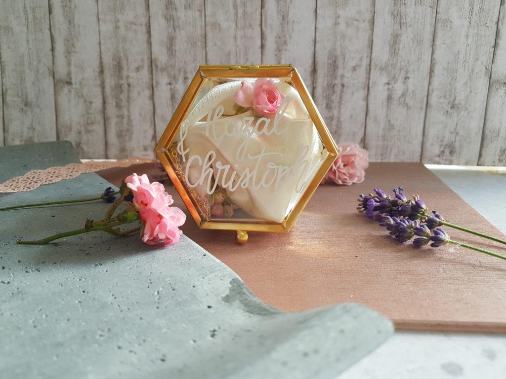 Sechseckige goldene Ringbox, mit transparenten Seiten und Deckel. Auf der Vorderseite sind die Namen des Brautpaares mit weißem Stift gelettert.